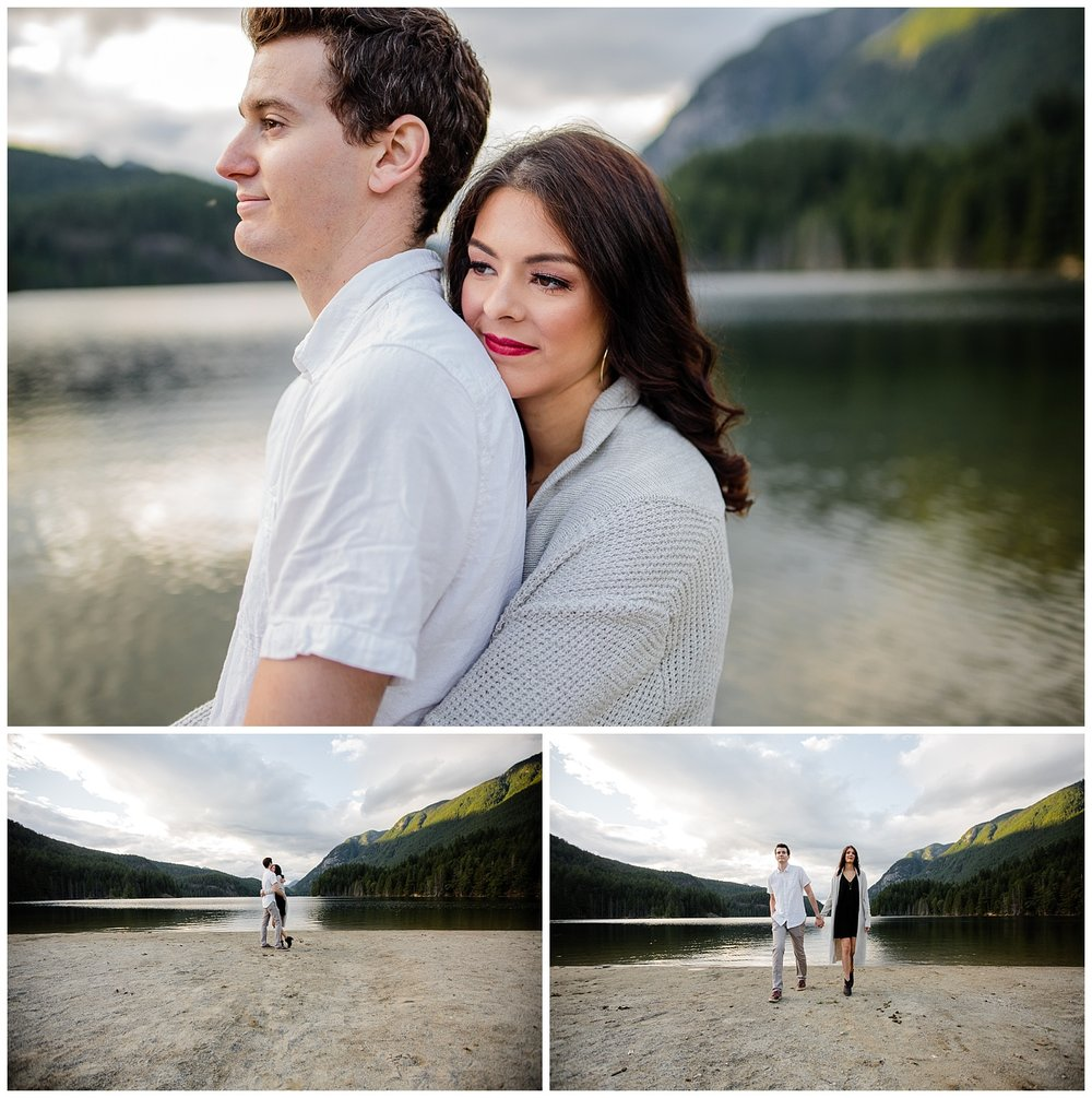 Couple standing on the beach of Buntzen Lake with mountains behind them during Buntzen Lake Anmore Port Moody Best and Fun Engagement Photo Shoot Mountain inspiration by Mimsical Photography best engagement photographer lower mainland vancouver British Columbia