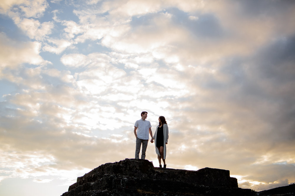couple standing on ruins holding hands sunset Old Orchard Hall Port Moody Engagement Photo Session by water wearing white button down shirt and black dress with hat during fun and romantic engagement photo shoot at Old Orchard Park in Port Moody, British Columbia by best couples photographer Mimsical Photography Vancouver Lower Mainland Mountain adventure couples