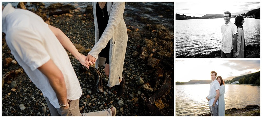 couple along water holding hands with sunset behind them Old Orchard Hall Port Moody Engagement Photo Session by water wearing white button down shirt and black dress with hat during fun and romantic engagement photo shoot at Old Orchard Park in Port Moody, British Columbia by best couples photographer Mimsical Photography Vancouver Lower Mainland Mountain adventure couples