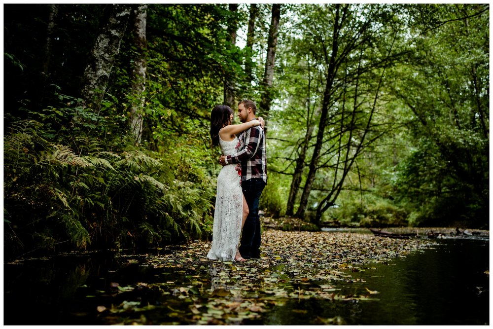 Williams Park Aldergrove Engagement Photographer Moody Fall Couple River Water Romantic Pose Yellow Leaves White Dress Dark_0012.jpg