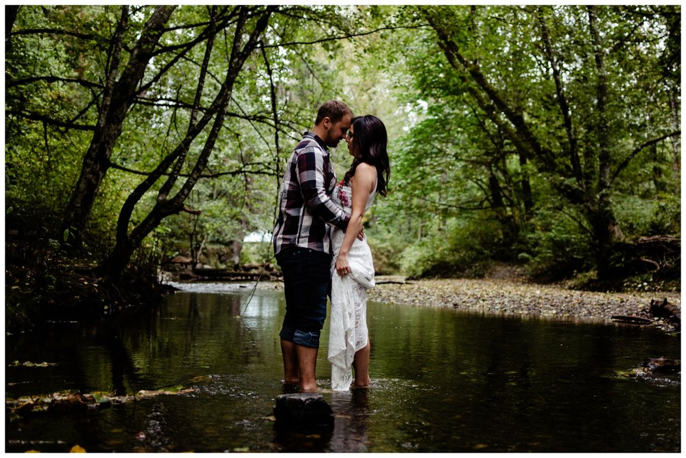Williams Park Aldergrove Engagement Photographer Moody Fall Couple River Water Romantic Pose Yellow Leaves White Dress Dark_0014.jpg