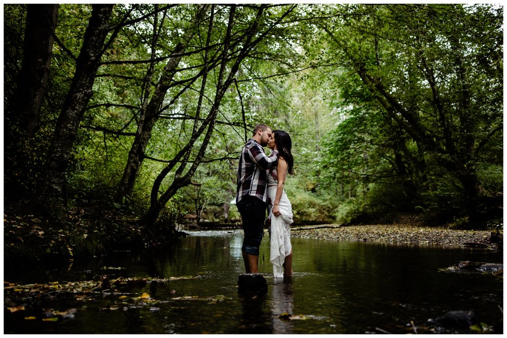 Williams Park Aldergrove Engagement Photographer Moody Fall Couple River Water Romantic Pose Yellow Leaves White Dress Dark_0017.jpg