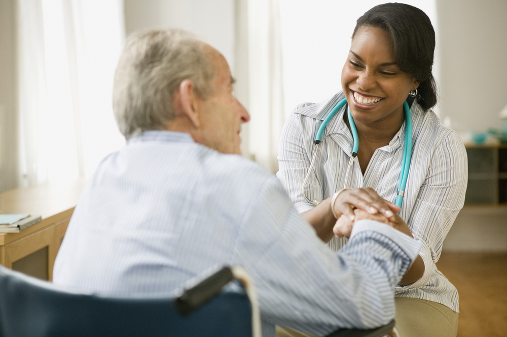 Nurse interacting with elderly patient in nursing home.