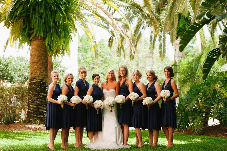 Snowball hydrangea and ivory garden rose bouquets pop against elegant navy cocktail dresses
