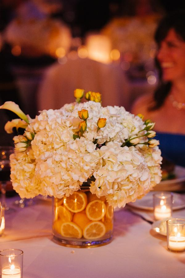 Cut lemons in small cylinder vases give a splash of color to an ivory centerpiece