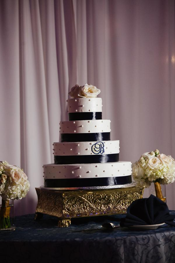 A buttercream confection topped with fresh flowers and accented with navy ribbon and a simple monogram