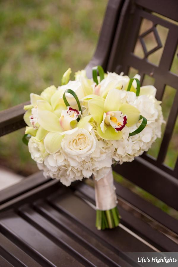 The brides bouquet featured white hydrangea, white roses, green cymbidium orchids, and loops of ribbon grass