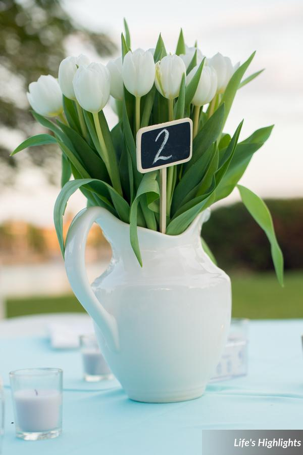 Assorted white ceramic pitchers filled with bunches of white tulips, hydrangea, and calla lilies,  also featured chalkboard stake table numbers