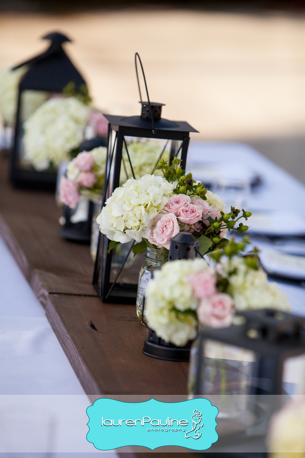 Tables featured wood plank runners dotted with assorted lanterns and mason jars of flowers