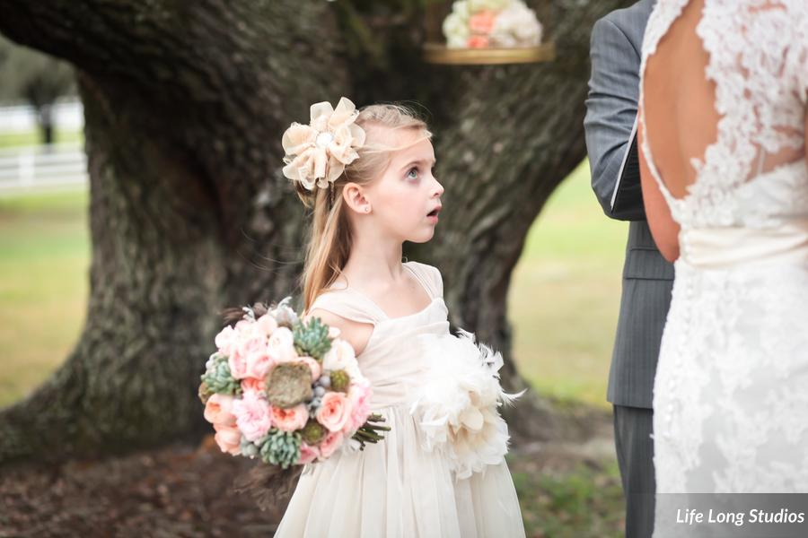 The groom's daughter, and flowergirl, held the bouquet while watching the ceremony in awe.