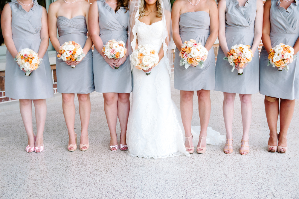 Bridesmaids wore mismatched grey cocktail dresses and carried bouquets in shades of ivory, pink, and peach