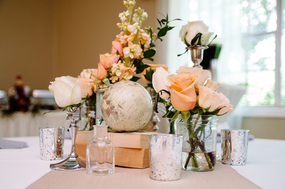 Centerpieces included stacked books, mason jars, bud vases, & candlesticks of flowers, & mercury glass votives