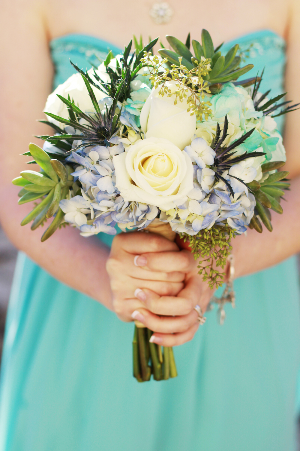 Bridesmaids carried bouquets of hydrangea, thistle, roses, succulents, and seeded eucalyptus