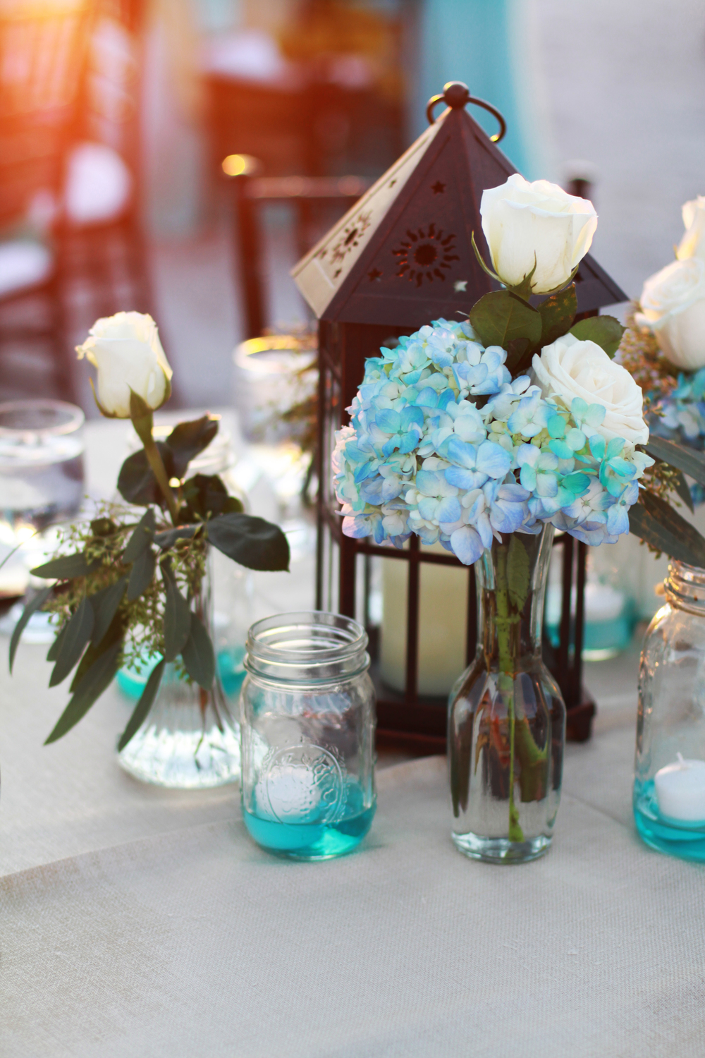 Centerpieces included lanterns surrounded by mason jars of flowers and floating candles in tinted water