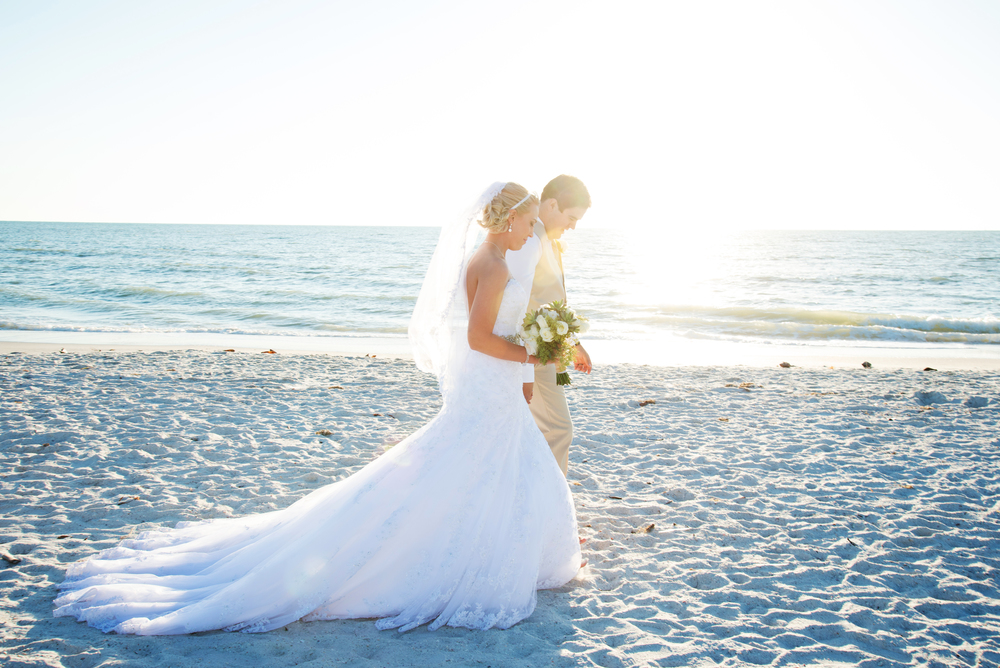 The bride and groom posed for photos on the beach during sunset