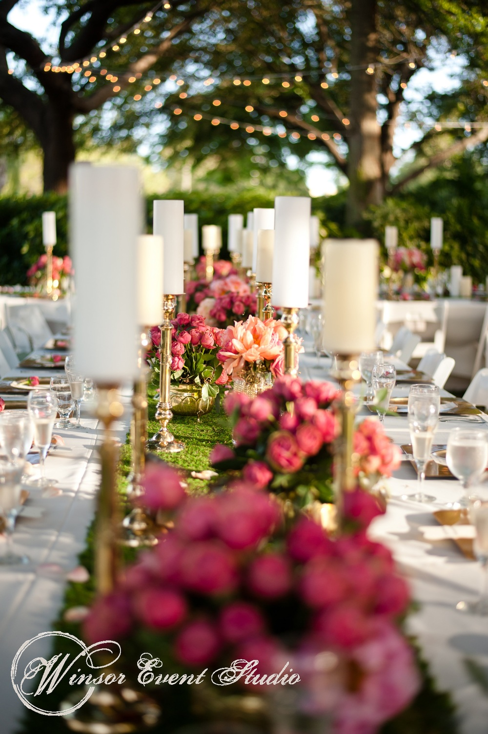 Bright coral flowers and gold candlesticks really popped against the moss table runners