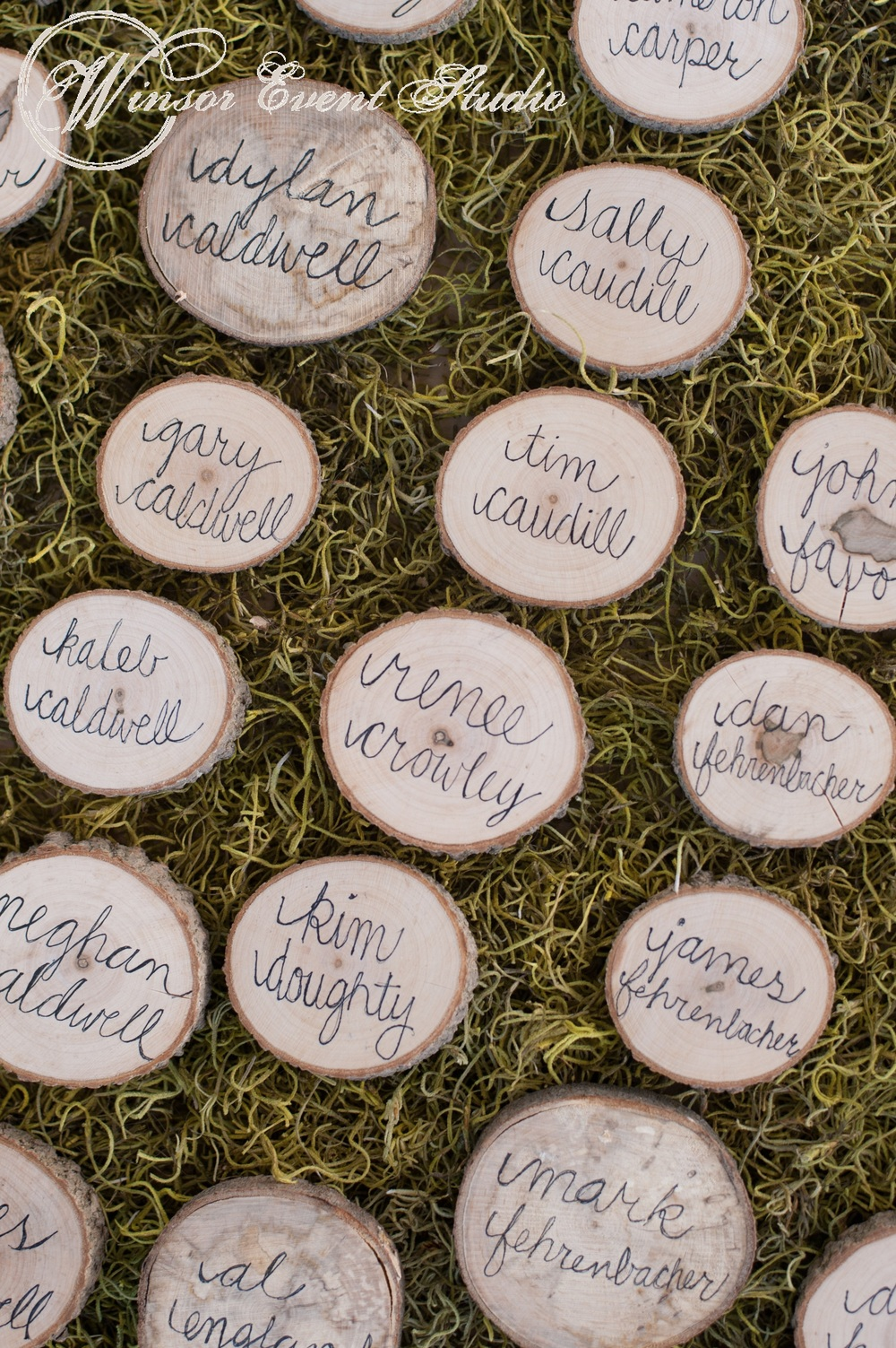Cut wood discs served as a unique escort card display atop a sheet of lush green moss