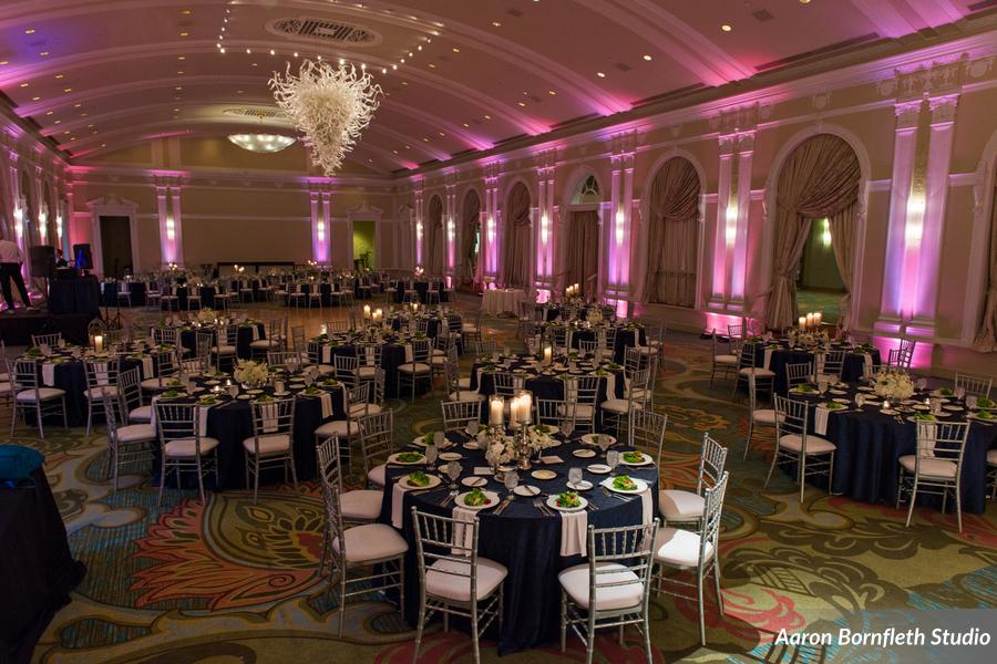 The ballroom was aglow with pink lighting, while silver chairs & candlesticks popped against the navy & white