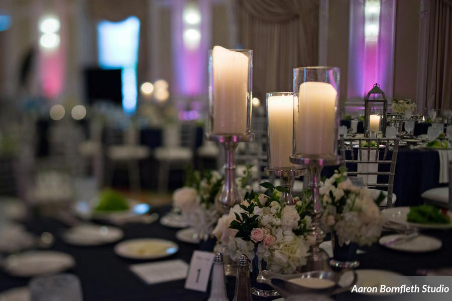 Silver candlesticks and lanterns mixed with lush white centerpieces made for classic centerpieces