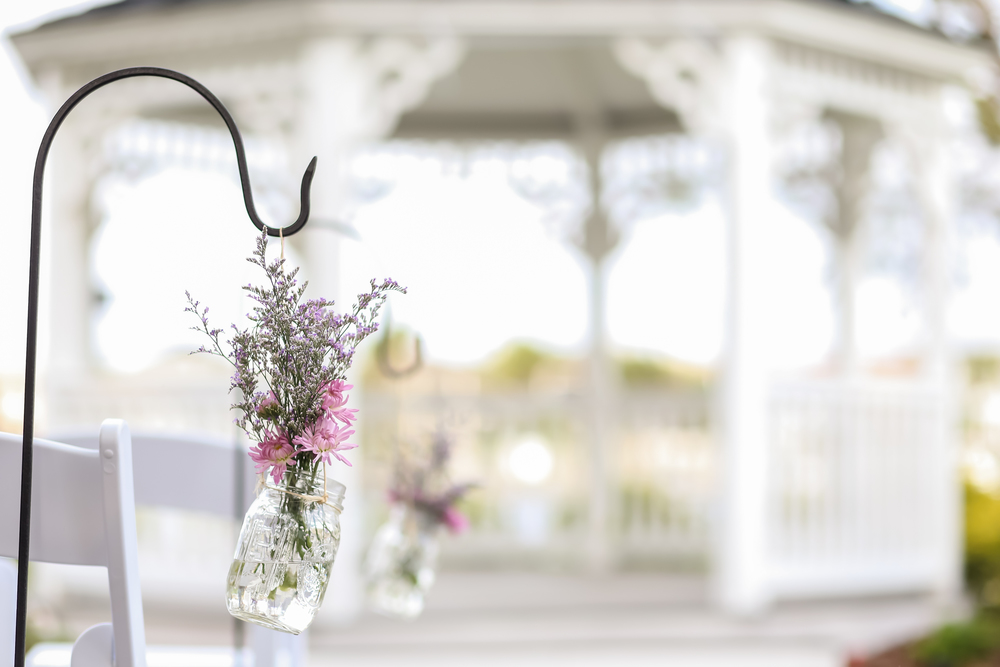 The aisle was lined with garden hooks and suspended mason jars filled with limonium and crysanthemums.