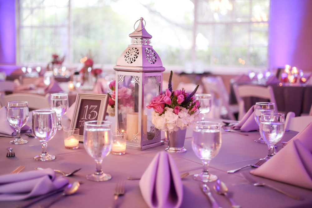 Tables dressed in silver linens with lavender napkins were surrounded by purple uplighting.
