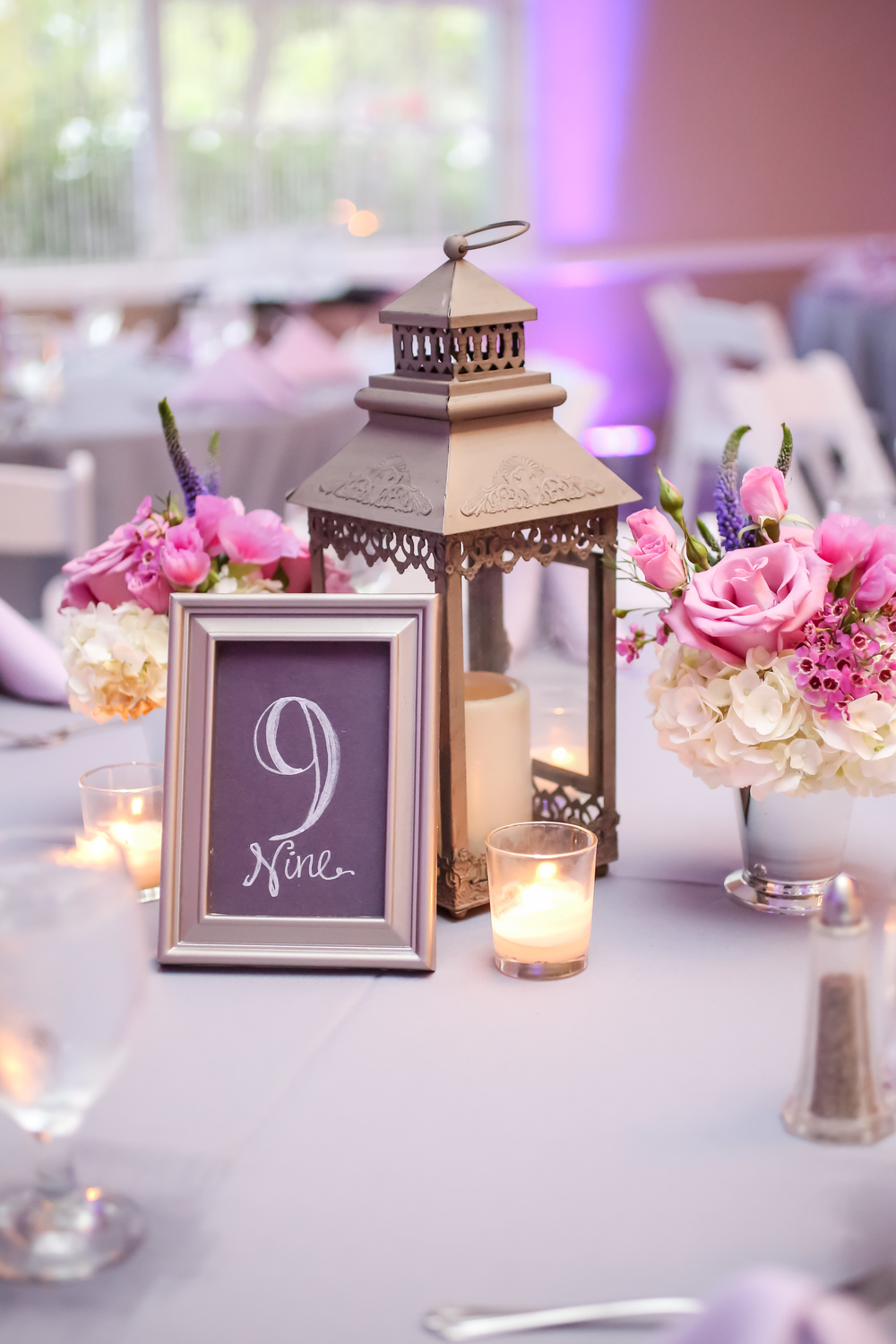 Some tables featured centerpieces of silver lanterns with julep cups of flowers and chalk table numbers.
