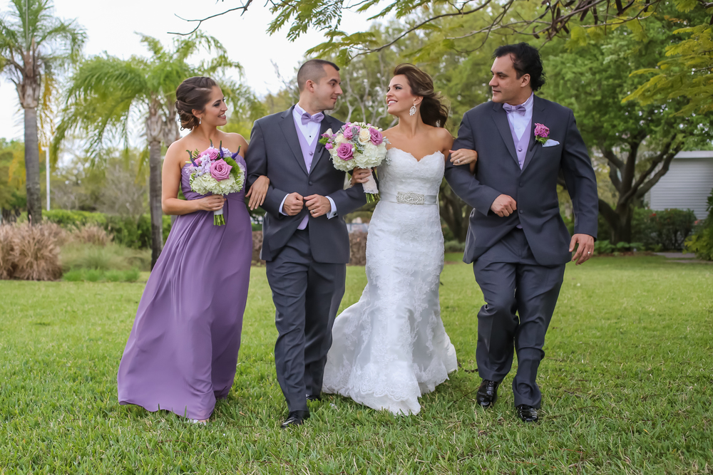 The maid of honor wore a lilac gown &gentlemen wore charcoal suits with purple vests &bowties.