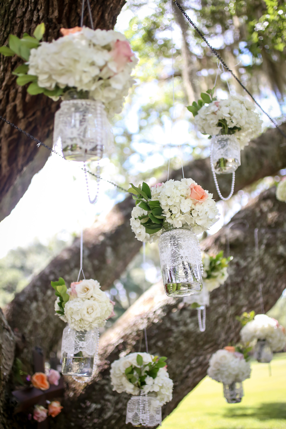 Lace-wrapped mason jars featured strands of pearls dripping from clusters of hydrangea and roses