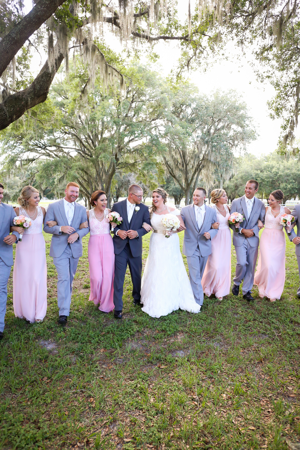 Bridesmaids wore lace and chiffon gowns in shades of soft pink, and gentlemen wore grey suits