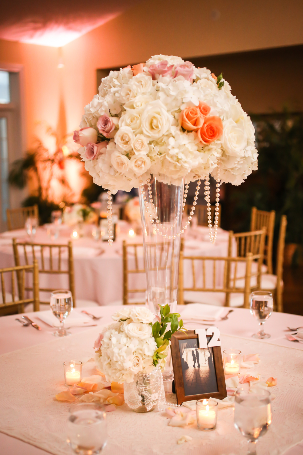 Centerpieces featured more strands of pearls cascading down from the abundent pastel roses and hydrangea