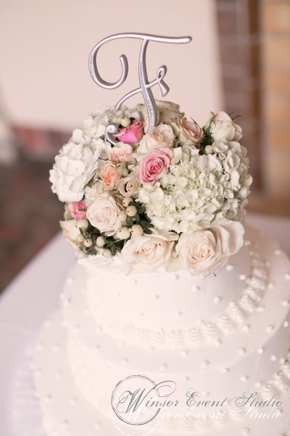 The buttercream dotted wedding cake (from Publix) was topped with fresh flowers and a silver monogram