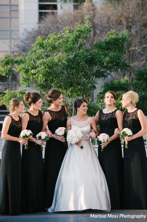 Bridesmaids wore classic black gowns and carried petite bouquets of blush and ivory roses