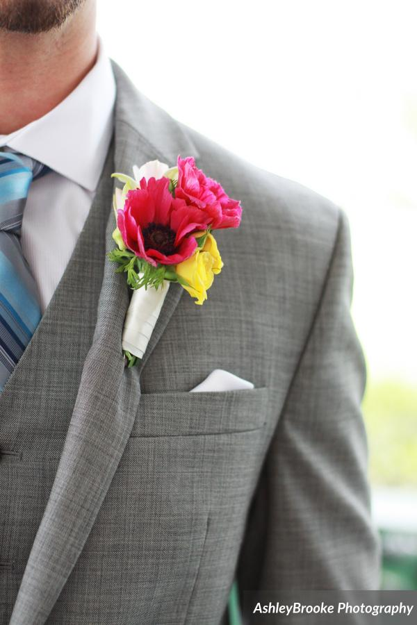 The groom's boutonniere combined pink anemones with yellow spray roses