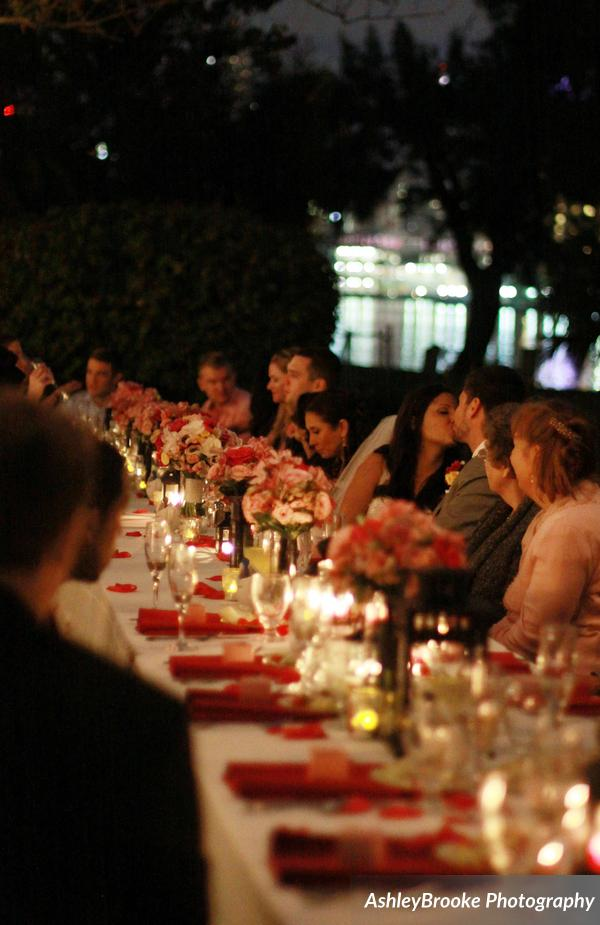 The wedding party were seated at a feasting table dotted with lanterns, candles, & bouquets