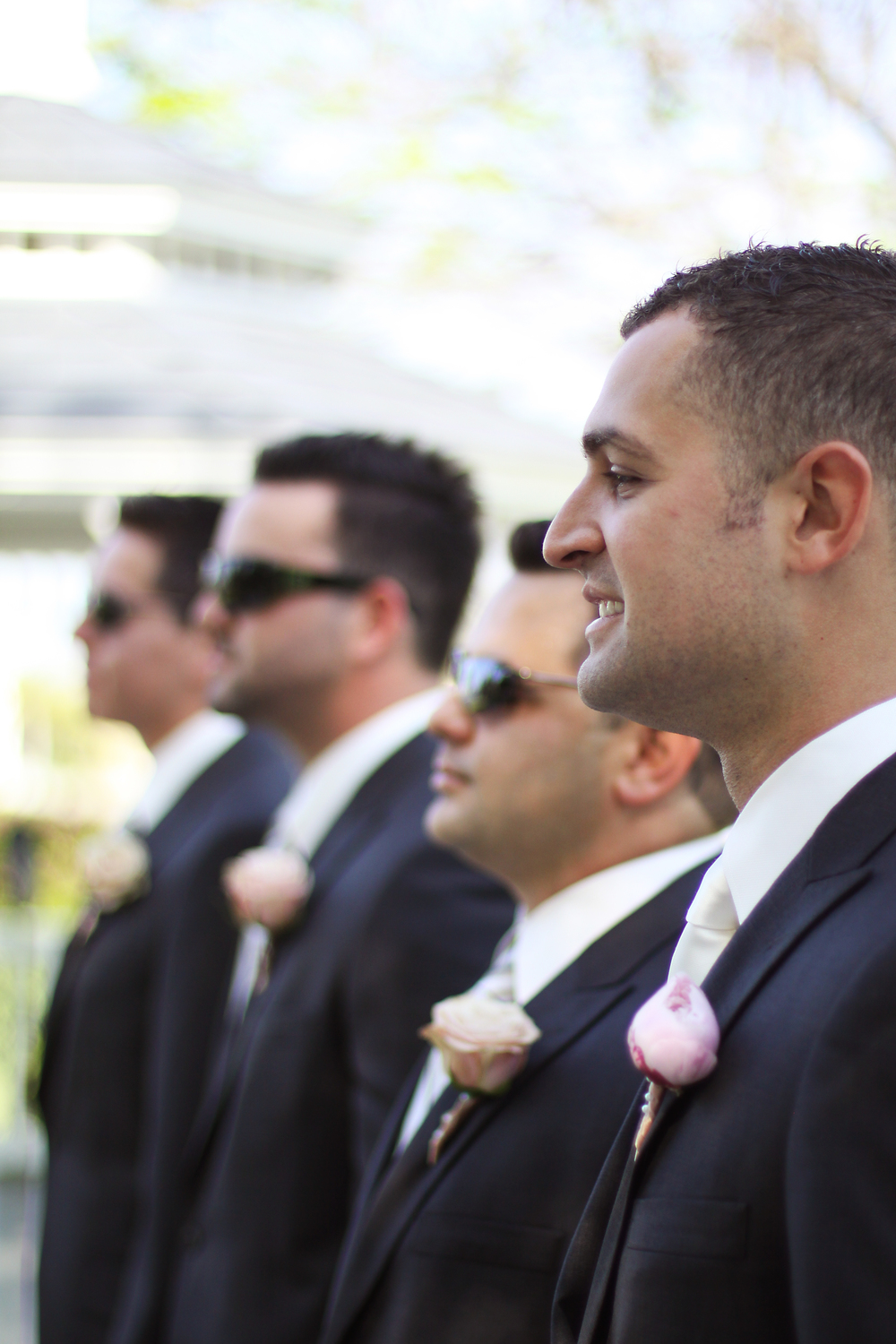 Guys wore classic black suits with blush rose and peony boutonnieres