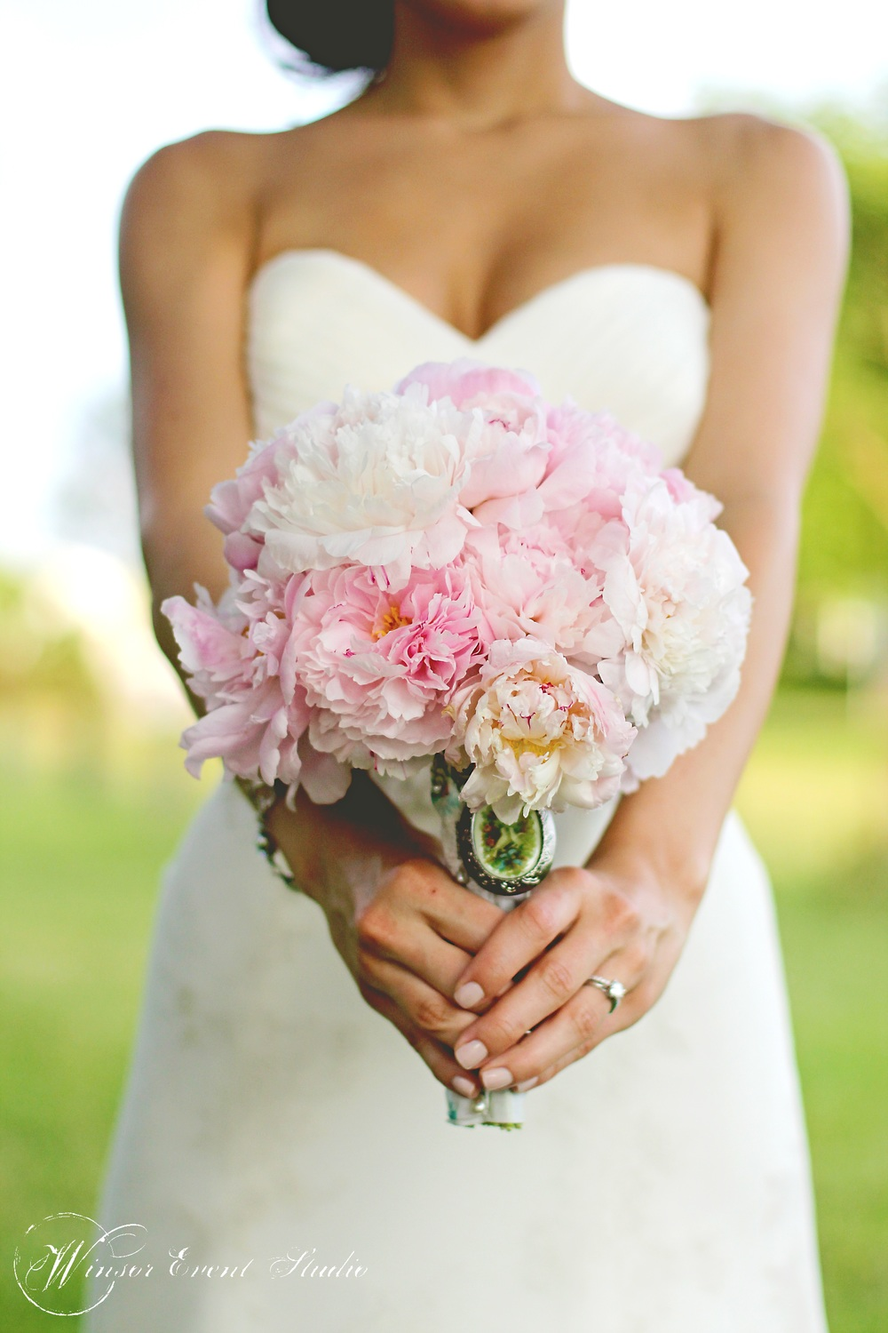 The bride carried a bouquet of blush and ivory peonies accented with a vintage brooch
