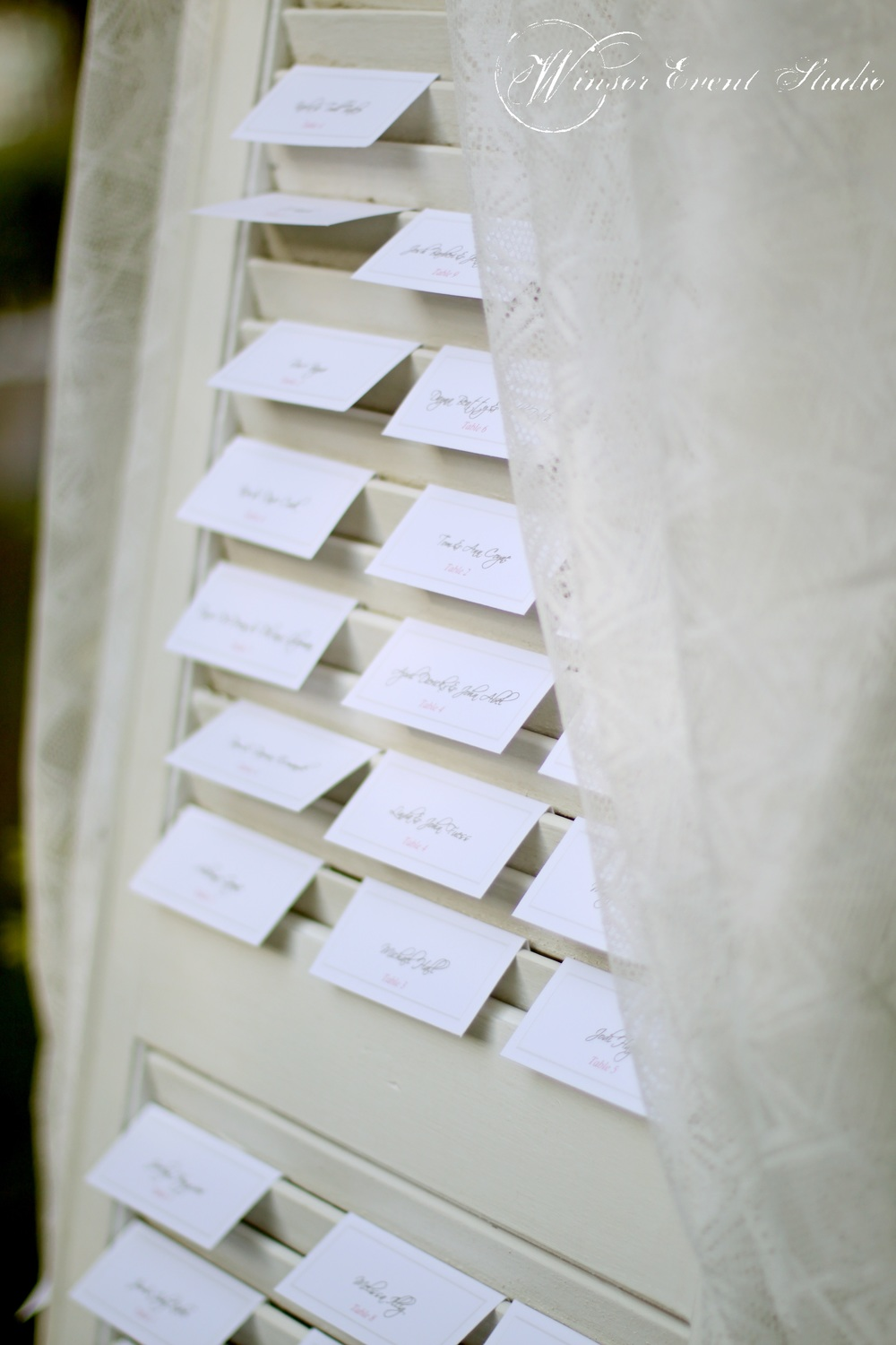 Escort cards were displayed in a vintage shutter draped with lace