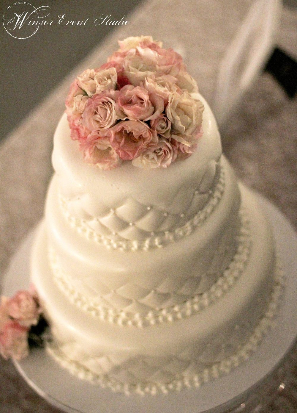 The wedding cake featured quilted fondant with pearl accents and blush spray roses
