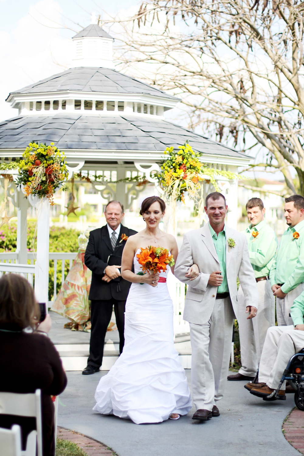 The gazebo was adorned with bright flora, raffia, and starfish