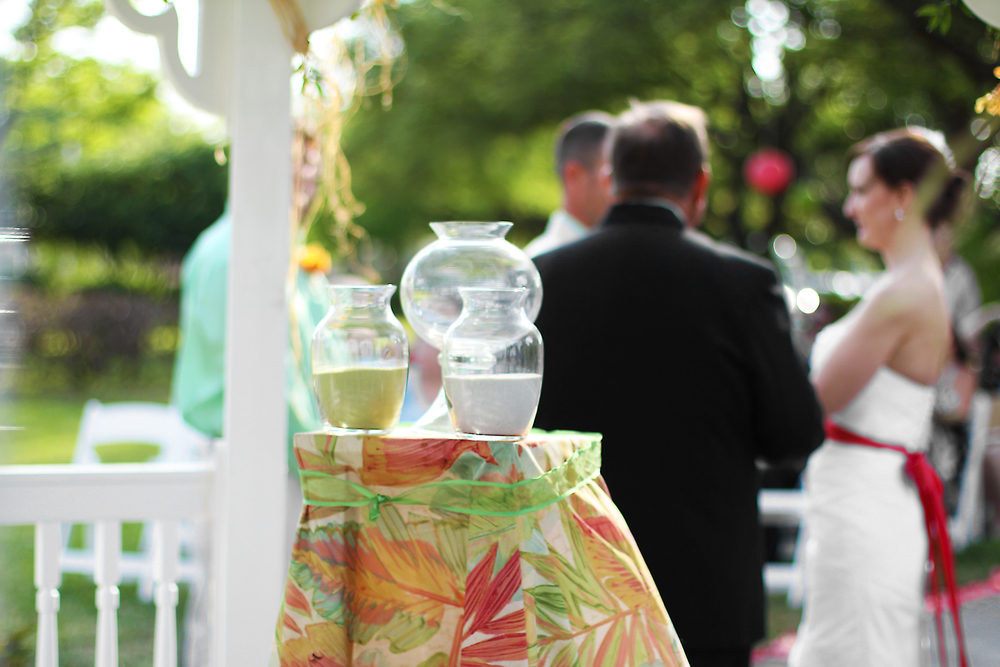 Decorative apothecary jars for the unity sand ceremony were display atop a colorful print linen