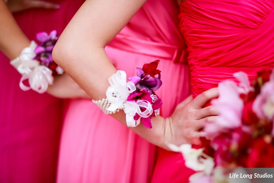 In addition to carrying paper parasols, bridesmaids wore pearl and orchid wristlet corsages