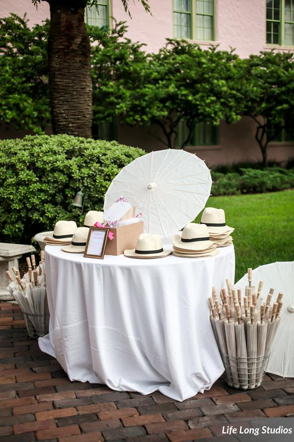 A shade station offered guests fedoras and parasols for the outdoor summer ceremony