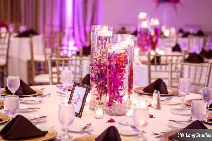 A trio of vases filled with submerged orchids and floating candles was surrounded by votives