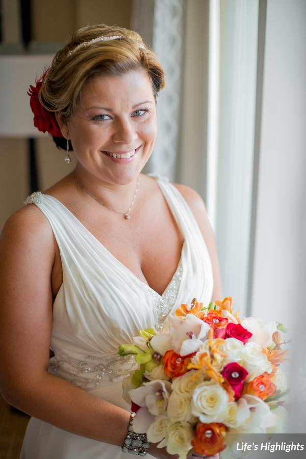 The bride's bouquet included pops of amber & ruby roses & orchids studded with rhinestones