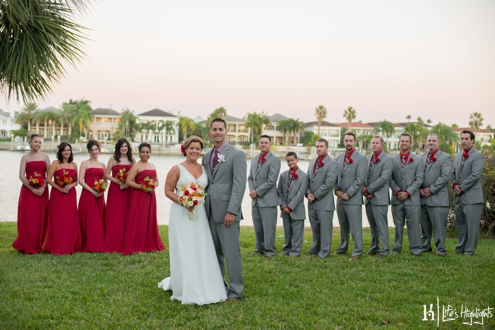 Groomsmen wore grey suits with ruby shirts to match the deep red bridesmaids dresses