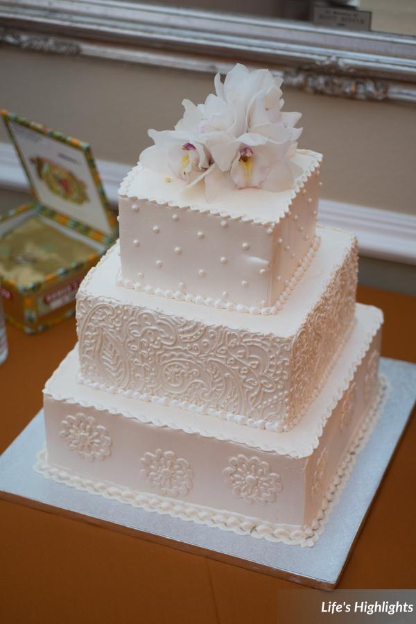 The buttercream wedding cake featured an ornate piped design and was topped with orchids