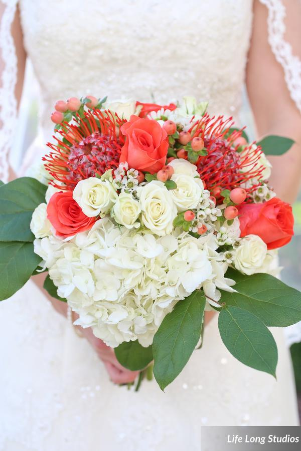 This bouquet combined hydrangea, roses, spray roses, waxflower, protea, and hypericum berries