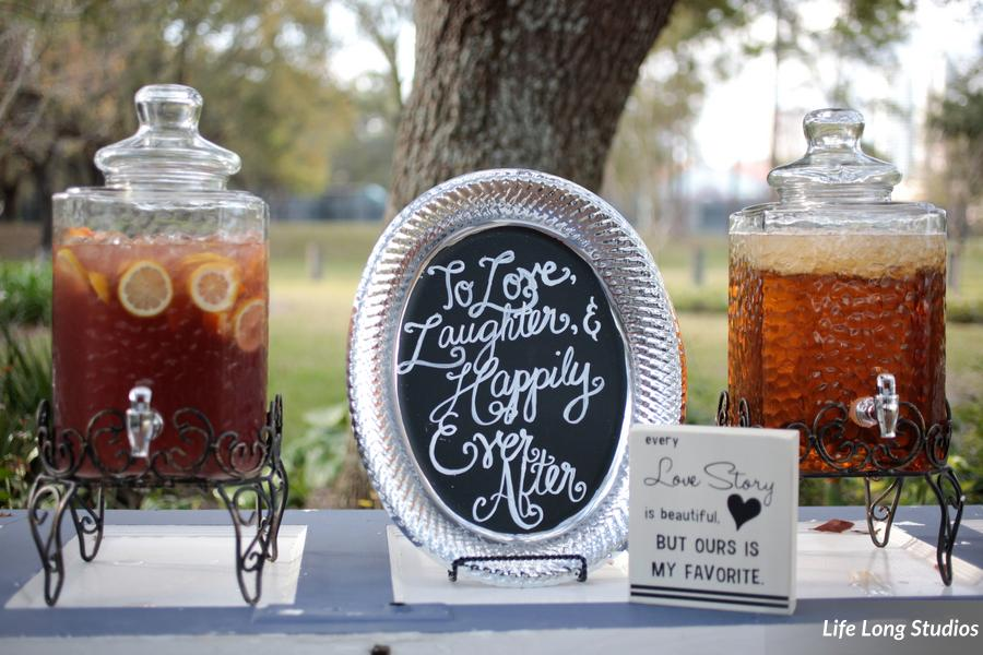 Chalk and wood signage accented a wood door table with iced tea in decorative dispensers