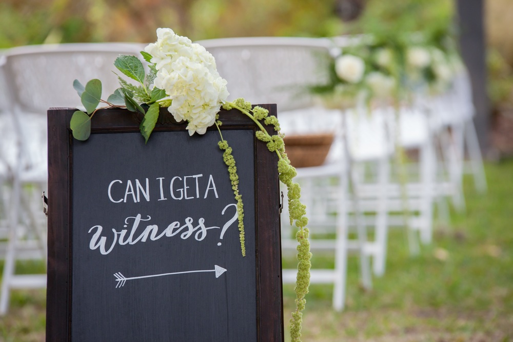 The garden ceremony featured a flora-adorned whitewashed wood arch in front of the Wedding Oak