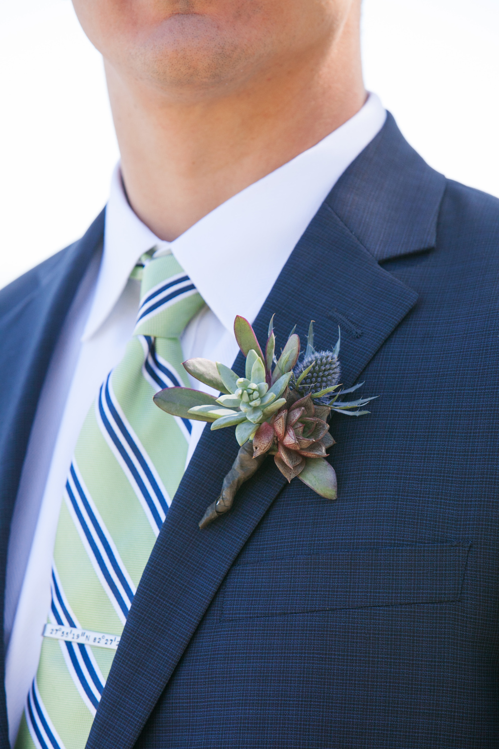 The groom wore a boutonniere of mini succulents and blue thistle